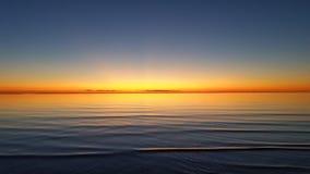 Härlig orange solnedgång på tyst havsvatten Royaltyfria Bilder
