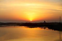 Härlig orange soluppgång och solen och dess reflexion i sjön Arkivfoto