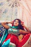 Härlig orientalisk kvinna i traditionell klänning som kopplar av som drömmer på soffan Royaltyfri Bild
