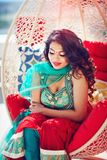 Härlig orientalisk kvinna i traditionell klänning som kopplar av som drömmer på soffan Arkivfoto