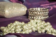 Härlig pärlemorfärg halsband på en purpurfärgad organza med ett armband Royaltyfria Bilder