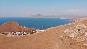 Härlig panoramautsikt av bergen och havet som filmar från över Flyg- skytte från shorelinen på ett soligt lager videofilmer