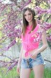 Härlig passformdam mellan blomningträdet fotografering för bildbyråer