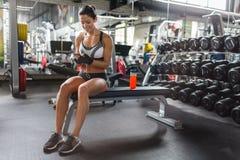 Härlig passformkvinna i idrottshall med Smartphone Fotografering för Bildbyråer