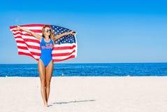 Härlig patriotisk gladlynt kvinna som rymmer en amerikanska flaggan på stranden Royaltyfria Bilder