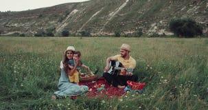 Härlig picknicktid med en ung familj, man som spelar på gitarren stock video