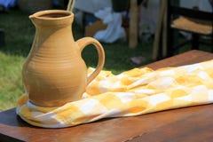 Härlig plats av Handcrafted krukmakerikannan på den gula och vita sjaletten Arkivbild