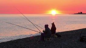 Härlig plats med fiskarekonturn med stångsammanträde på havsstranden arkivfilmer