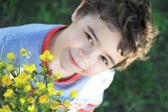 Härlig pojke med vildblommor Arkivfoton