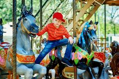 Härlig pojke som poserar på karusellen Ett barn i staden parkerar på ritterna royaltyfri bild