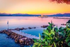Härlig port av den Nafplio staden i Grekland med små fartyg, palmträd och Bourtzi rockerar på vattnet Royaltyfri Foto