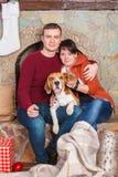 Härlig portrain av den unga familjen med den gulliga beaglehunden på helgdagsaftonen för nytt år arkivfoto