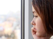 Härlig pre-tonårig eftertänksam flicka som ut ser till fönstret Royaltyfri Bild