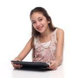 Härlig pre-tonårig flicka med en minnestavladator Arkivbilder