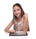 Härlig pre-tonårig flicka med en minnestavladator Royaltyfria Foton