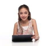 Härlig pre-tonårig flicka med en minnestavladator Arkivfoton