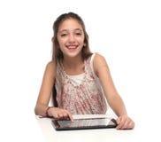 Härlig pre-tonårig flicka med en minnestavladator Arkivfoto