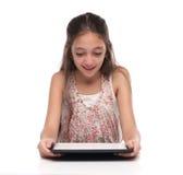 Härlig pre-tonårig flicka med en minnestavladator Royaltyfri Bild