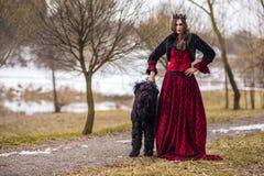 Härlig prinsessa i röd klänning och svarta pälsomslaget som poserar i krona tillsammans med hennes hund i Forest During Early Spr arkivbild