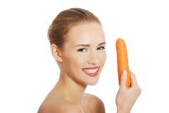 Härlig profil av den caucasian kvinnan som äter den rå nya moroten. Arkivbilder