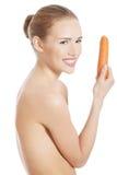Härlig profil av den caucasian kvinnan som äter den rå nya moroten. Royaltyfri Fotografi