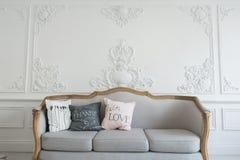 Härlig Provance vardagsrum med soffan över den lyxiga väggen dekorerade med stuckaturstöpningar Royaltyfri Fotografi
