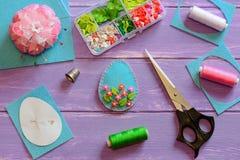 Härlig prydnad för påskägg med plast-blommor och sidor Filtäggprydnad, pappers- mall, sax arkivfoto
