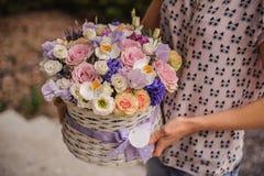 Härlig purpurfärgad bukett av blandade blommor i korghåll av kvinnan Royaltyfri Foto