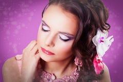 Härlig purpurfärgad makeup på flickan med stängda ögon på lilor Arkivfoto