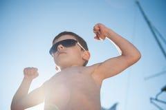 Härlig pys i solglasögon som visar hans muskel i solig dag för sommar Royaltyfri Foto