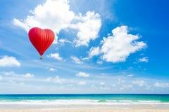 Härlig röd ballong i formen av en hjärta på den Karon stranden royaltyfria foton