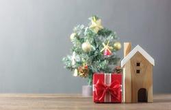 Härlig röd gåvaask och trävitt hus Suddighetsbakgrundsjulgran och garnering & prydnad arkivfoto