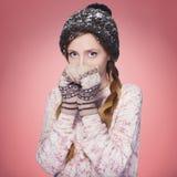 Härlig röd hårkvinna i vinterdräkt: varm tröja, halsduk och hatt med snö över hela henne Isolerat på rosa rött Royaltyfria Foton