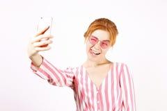 Härlig röd hövdad ung kvinna som poserar, visar emotionella ansiktsuttryck och gör roliga framsidor med mobiltelefonen royaltyfri bild