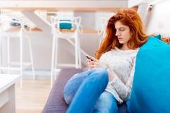 Härlig röd haired kvinna som använder telefonen Royaltyfria Bilder