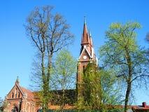 Härlig röd kyrka i våren, Litauen royaltyfri bild