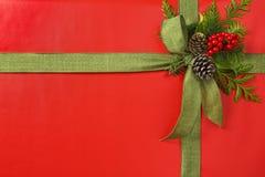 Härlig röd och grön julgåva som är närvarande med tygbandpilbågen och botaniska garneringar Horisontalbakgrundsgräns royaltyfria bilder