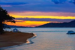 Härlig rödaktig himmel under solnedgången kust arkivbild