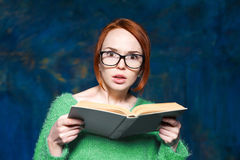 Härlig rödhårig flicka i en grön tröja och exponeringsglasläsebok Royaltyfria Foton