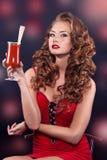 Härlig rödhårig flicka i en röd coctailklänning Royaltyfria Bilder