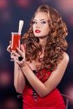 Härlig rödhårig flicka i en röd coctailklänning Arkivfoton