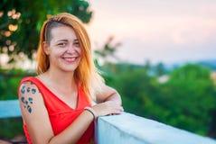 Härlig rödhårig flicka i en röd klänning och tatuerade skratt på verandan av en sommarrestaurang Arkivfoto