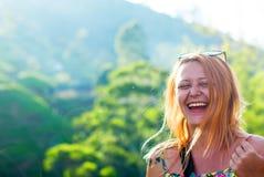 Härlig rödhårig flicka med rakade tempel som skrattar med lycka mot bakgrunden av berg Royaltyfri Fotografi