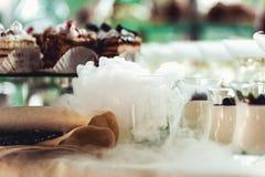 Härlig radlinje av olika kulöra alkoholcoctailar på ett parti, whiskykonjak, torr is för starksprit arkivbild