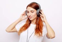 Härlig redhairkvinna i hörlurar som lyssnar till musik royaltyfri foto