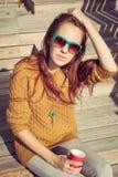 Härlig redheaded flicka i solglasögon som sitter på träbräden på en varm sommarafton Arkivbild