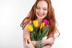 Härlig redheaded flicka med buketten av tulpan Arkivfoton