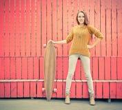 Härlig redheaded flicka som rymmer en longboard som står nära den röda väggen Royaltyfri Bild