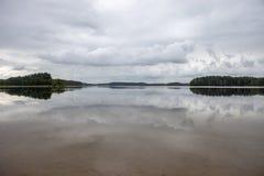 Härlig reflexion av en skog och en molnig himmel på vattnet Arkivbild