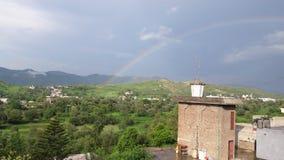 Härlig regnbåge med grönt landskap arkivfoton
